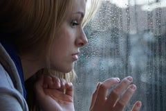 Mujer joven triste que mira a través de ventana en día lluvioso imagenes de archivo