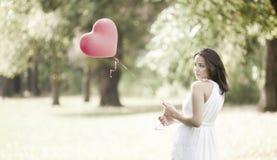 Mujer joven triste que se coloca con un globo formado rojo del corazón Imagen de archivo libre de regalías