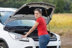 Mujer joven triste que se inclina en el motor del Ca quebrado en campo y que mira in camera Fotografía de archivo libre de regalías