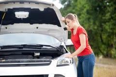 Mujer joven triste que se inclina en la capilla abierta de su coche quebrado en el camino del campo Foto de archivo libre de regalías