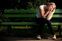 Mujer joven triste que se sienta en banco en parque Foto de archivo