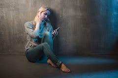 Mujer joven triste que se sienta en el piso con un teléfono en manos Llamada en espera, ninguna conexión Fotografía de archivo