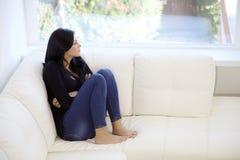 Mujer joven triste que se sienta en el sofá que mira hacia fuera la ventana Foto de archivo