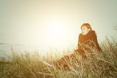 Mujer joven triste que se sienta en la hierba que siente tan triste y el loneline Fotos de archivo