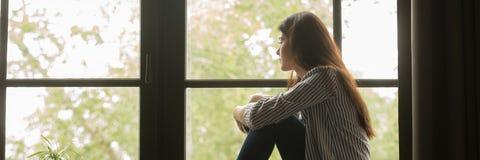 Mujer joven triste que se sienta mirando hacia fuera la ventana y el pensamiento fotos de archivo libres de regalías