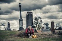 Mujer joven triste sola en el luto delante de una lápida mortuaria Imagen de archivo libre de regalías