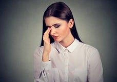 Mujer joven triste subrayada en una situación desesperada que mira abajo Foto de archivo libre de regalías