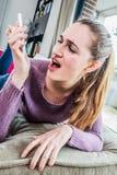 Mujer joven ultrajada que mira su teléfono móvil con la irritación Imagen de archivo libre de regalías