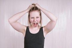 Mujer joven ultrajada que tiene una rabieta del genio que grita y que grita fotografía de archivo libre de regalías