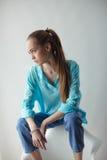 Mujer joven urbana elegante confiada que parece ausente mientras que se sienta en silla, en fondo gris Foto de archivo