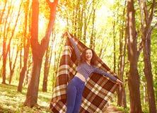 Mujer joven urbana moderna hermosa que sostiene una tela escocesa en bosque Foto de archivo