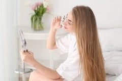 Mujer joven usando el bigudí de la pestaña en casa foto de archivo libre de regalías