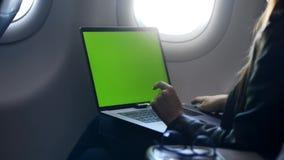 Mujer joven usando el ordenador portátil, enviando el correo electrónico en aeroplano metrajes