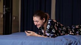 Mujer joven usando el teléfono elegante de la célula Mentira sonriente de la mujer feliz en cama en dormitorio almacen de metraje de vídeo
