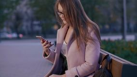 Mujer joven usando el teléfono móvil que se sienta en banco en la igualación de la ciudad moderna del parque almacen de metraje de vídeo