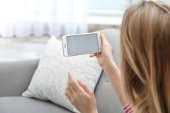 Mujer joven usando la charla video en smartphone en sala de estar Espacio para el dise?o fotos de archivo libres de regalías