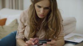 Mujer joven usando la tarjeta de crédito para el pago en el teléfono Paga de la persona femenina en línea metrajes