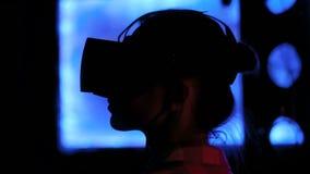 Mujer joven usando las auriculares de la realidad virtual en la exposición interactiva oscura almacen de metraje de vídeo