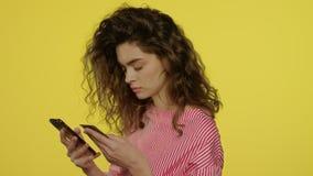 Mujer joven usando los apps del dinero en el smartphone para la tarjeta de banco de la paga en estudio amarillo metrajes