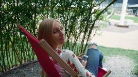 Mujer joven usando smartphone en gazebo de la planta almacen de metraje de vídeo
