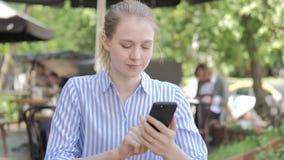 Mujer joven usando Smartphone que se sienta en terraza del café almacen de video