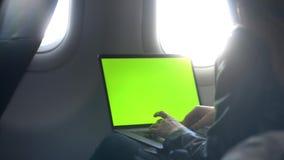 Mujer joven usando su ordenador portátil moderno en aeroplano almacen de video
