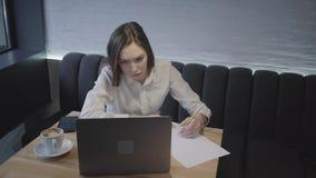 Mujer joven usando su ordenador portátil que se sienta en la tabla en café Muchacha que se sienta en el sofá con una taza de café almacen de video