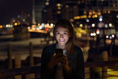 Mujer joven usando su smartphone durante la noche luz de la ciudad como fondo fotos de archivo libres de regalías