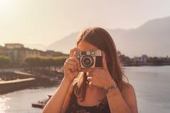 Mujer joven usando una c?mara del vintage delante de la 'promenade' del lago en Ascona foto de archivo libre de regalías