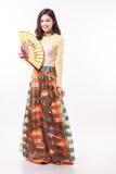 Mujer joven vietnamita hermosa con el estilo moderno ao dai que sostiene una fan de papel en el fondo blanco Imagen de archivo