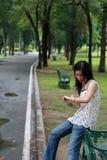 Mujer joven watting alguien en el parque Foto de archivo libre de regalías
