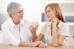 Mujer joven y abuela que charlan en casa Imágenes de archivo libres de regalías