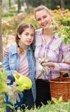 Mujer joven y adolescente felices con las herramientas que cultivan un huerto adentro al aire libre Fotografía de archivo libre de regalías