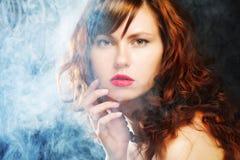 Mujer joven y atractiva en humo Imagen de archivo libre de regalías