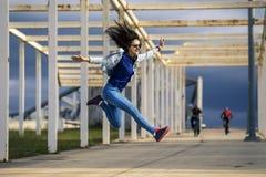 Mujer joven y atractiva en salto con el pelo rizado y la cara feliz Imágenes de archivo libres de regalías