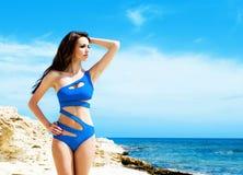 Mujer joven y atractiva en un traje de baño azul en la playa Fotografía de archivo libre de regalías