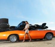Mujer joven y atractiva que presenta cerca de un coche del músculo imagen de archivo libre de regalías