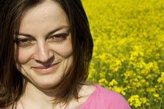 Mujer joven y campo de flor amarillo Imagenes de archivo