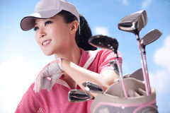 Mujer joven y clubs de golf Foto de archivo