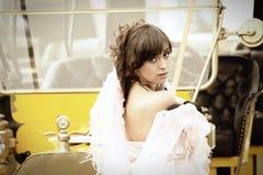 Mujer joven y coche retro amarillo Imágenes de archivo libres de regalías
