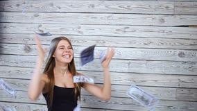 Mujer joven y dinero que cae almacen de video