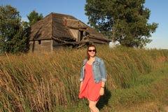 Mujer joven y edificio que se derrumba en un día ventoso del país Imagen de archivo libre de regalías