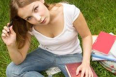 Mujer joven y encantadora con el pelo largo, sosteniendo el libro, pensando Foto de archivo