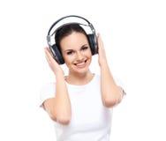 Mujer joven y feliz en los auriculares aislados en blanco Imagen de archivo libre de regalías