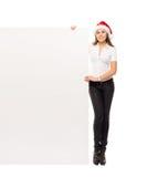 Mujer joven y feliz en un sombrero de Christmss con una bandera Foto de archivo libre de regalías