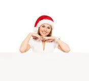 Mujer joven y feliz en un sombrero de Christmss con una bandera Imagenes de archivo