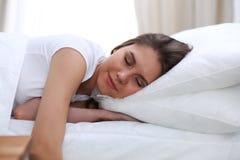 Mujer joven y feliz hermosa que duerme mientras que miente en cama comfortablemente y dichosamente sonríe imagen de archivo libre de regalías