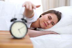 Mujer joven y feliz hermosa que duerme mientras que miente en cama comfortablemente y dichosamente sonríe foto de archivo