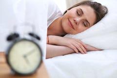 Mujer joven y feliz hermosa que duerme mientras que miente en cama comfortablemente y dichosamente sonríe imagen de archivo
