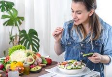 Mujer joven y feliz que come la ensalada en la tabla imagen de archivo